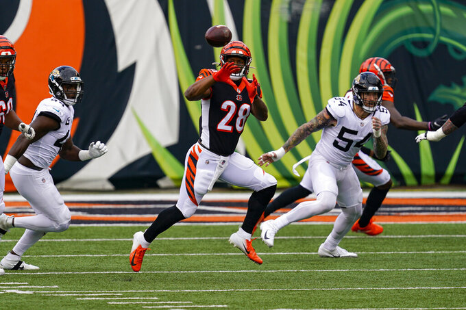 Cincinnati Bengals running back Joe Mixon (28) makes catch in front of Jacksonville Jaguars defensive end Cassius Marsh (54) in the first half of an NFL football game in Cincinnati, Sunday, Oct. 4, 2020. (AP Photo/Bryan Woolston)
