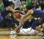 California's Paris Austin, left, and Audre Kelly, right, try to get the ball from Oregon's Kenny Wooten, center, during the first half of an NCAA college basketball game Wednesday, Feb. 6, 2019, in Eugene, Ore. (AP Photo/Chris Pietsch)