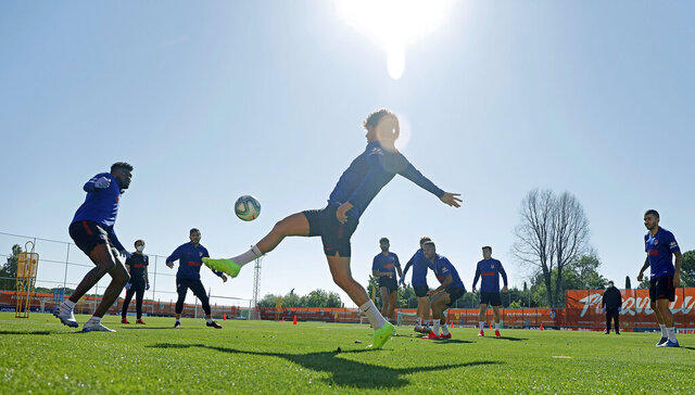 In this photo provided by Atletico Madrid, team players take part in the first group training session in Madrid, Spain, Monday May 18, 2020. All Spanish league clubs can begin group training sessions this week despite stricter lockdown restrictions remaining in place in parts of Spain because of the coronavirus pandemic. (Atletico de Madrid via AP)