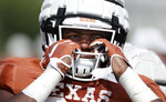 Texas running back Keaontay Ingram adjusts his helmet during a morning practice at the team's facility in Austin, Texas, Wednesday, Aug. 7, 2019. (AP Photo/Eric Gay)
