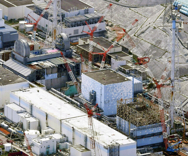 FILE - This Sept. 4, 2017, aerial file photo shows Fukushima Dai-ichi nuclear power plant's reactors, from bottom at right, Unit 1, Unit 2 and Unit 3, in Okuma, Fukushima prefecture, northeastern Japan. A draft investigation report into the 2011 Fukushima nuclear meltdown, adopted by Japanese nuclear regulators Wednesday, Jan. 27, 2021, says it has detected dangerously high levels of radioactive contamination at two of the three reactors, adding to concerns about decommissioning challenges. The interim report said data collected by investigators showed that the sealing plugs sitting atop the No. 2 and 3 reactor containment vessels were as fatally contaminated as nuclear fuel debris that had melted and fell to the bottom of the reactors following the March 2011 tsunami and earthquake. (Daisuke Suzuki/Kyodo News via AP, File)