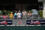 Baseball fans watch from a distance as the Atlanta Braves workout during spring training baseball practice on Tuesday, Feb. 23, 2021, in North Port, Fla. (AP Photo/Brynn Anderson)