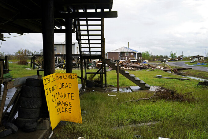 Storm clouds from Tropical Storm Nicholas are seen behind homes of the vanishing Native American community of Isle de Jean Charles, La., which were destroyed by Hurricane Ida, Tuesday, Sept. 14, 2021. (AP Photo/Gerald Herbert)