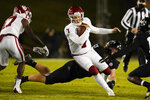 Oklahoma quarterback Spencer Rattler (7) breaks a tackle by Iowa State linebacker Mike Rose (23) during the first half an NCAA college football game, Saturday, Oct. 3, 2020, in Ames, Iowa. (AP Photo/Charlie Neibergall)