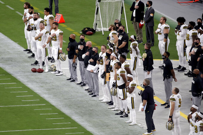 New Orleans Saints plays stand during the national anthem before an NFL football game against the Las Vegas Raiders, Monday, Sept. 21, 2020, in Las Vegas. (AP Photo/Isaac Brekken)