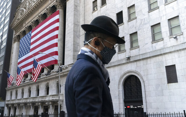 FILE - In this Nov. 16, 2020 file photo a man wearing a mask passes the New York Stock Exchange in New York. Stocks are opening moderately lower on Wall Street, edging below the record highs they set a day earlier. The S&P 500 fell 0.4% shortly after the opening bell Wednesday, Dec. 2. (AP Photo/Mark Lennihan, File)