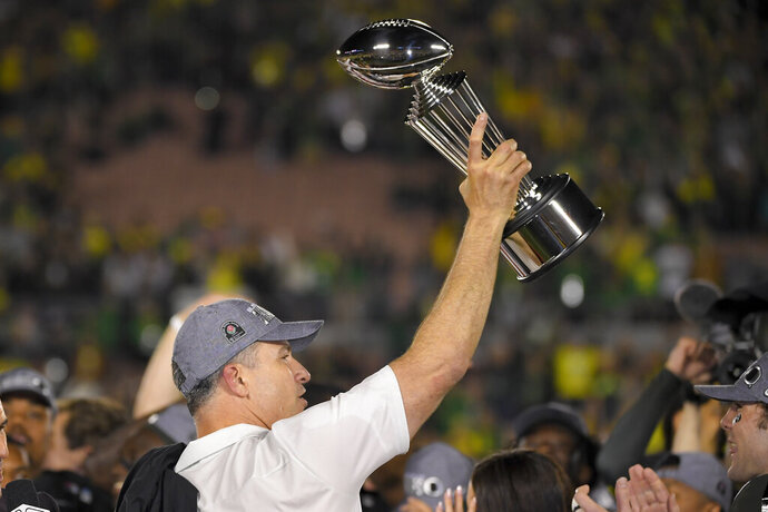 Oregon head coach Mario Cristobal celebrates with the trophy after the Rose Bowl NCAA college football game against Wisconsin Wednesday, Jan. 1, 2020, in Pasadena, Calif. (AP Photo/Mark J. Terrill)