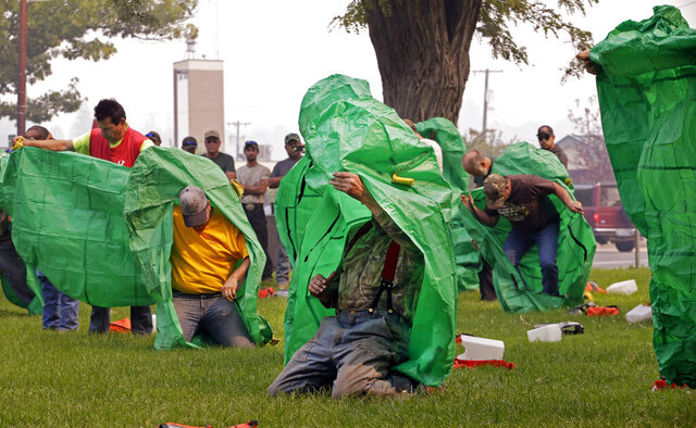 FILE - In this Aug. 22, 2015 file photo, volunteers learn to deploy fire shelters with practice equipment after a callout by fire officials seeking to supplement their usual resources in Omak, Wash. After flames trapped 14 firefighters in California and they had to use last-resort fire shelters to survive, questions are emerging about how well the emergency devices work and how often they are used while crews fight wildfires. (AP Photo/Elaine Thompson, File)