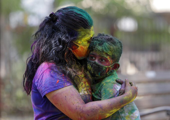 An Indian woman smeared in colors and wearing mask embraces her child during Holi festival celebrations in Mumbai, India, Monday, March 29, 2021. Hindus threw colored powder and sprayed water in massive Holi celebrations Monday despite many Indian states restricting gatherings to try to contain a coronavirus resurgence rippling across the country. (AP Photo/Rajanish Kakade)