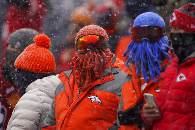 A Denver Broncos fan covers his face as snow falls during the first half of an NFL football game against the Kansas City Chiefs, Sunday, Oct. 25, 2020, in Denver. (AP Photo/David Zalubowski)
