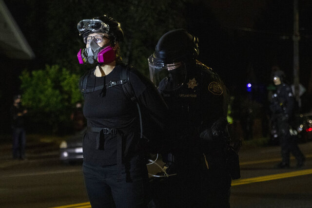 Portland police make arrests on the scene of the nightly protests at a Portland police precinct on Sunday, Aug. 30, 2020 in Portland, Ore. Oregon State Police will return to Portland to help local authorities after the fatal shooting of a man following clashes between President Donald Trump supporters and counter-protesters that led to an argument between the president and the city's mayor over who was to blame for the violence. (AP Photo/Paula Bronstein)