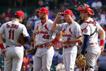 St. Louis Cardinals manager Mike Shildt, second from right, talks with shortstop Paul DeJong, left, first baseman Paul Goldschmidt, second from left, and catcher Andrew Knizner, right, as they wait for relief pitcher Andrew Miller during the sixth inning of a baseball game against the Chicago Cubs in Chicago, Sunday, Sept. 26, 2021. (AP Photo/Nam Y. Huh)