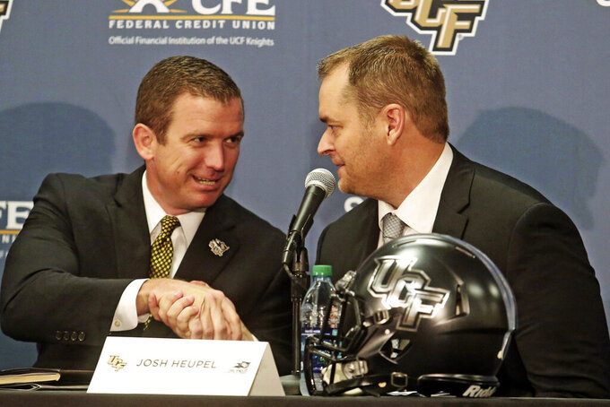 FILE - In this Dec. 5, 2017, file photo, Josh Heupel, right, is introduced as the new Central Florida head football coach by Danny White, UCF Athletic director,  in Orlando, Fla. Josh Heupel is leaving UCF to become the next Tennessee coach, a person with knowledge of the situation told The Associated Press on Wednesday, Jan. 27, 2021. Tennessee hired Danny White away from UCF as its athletic director last Thursday, and his first job was finding a new football coach to replace Jeremy Pruitt, who was fired Jan. 18.(Red Huber/Orlando Sentinel via AP, File)