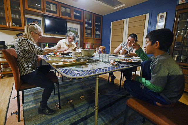 Roslyn and David Zinner, from left, eat dinner with Stephanie and her son Samir, in Columbia, Md., Jan. 4, 2021. The Zinners have elected to sponsor the asylum-seeking family from Honduras and have been living together for almost two years. The Howard County couple are among a small network of families across the country who are welcoming asylum-seekers like the Honduran family into their homes for long-term stays. (Kenneth K. Lam/The Baltimore Sun via AP)