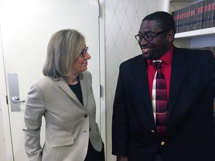 Sauntore Thomas, right, and his lawyer, Deborah Gordon, left, talk, Thursday, Jan. 23, 2020 in Bloomfield Hills, Mich. Thomas, a black Air Force veteran who tried to deposit settlement checks from a discrimination lawsuit was rejected by his suburban Detroit bank, which suspected fraud and called police. After settling a lawsuit with his former employer, Sauntore Thomas now is suing TCF Bank, alleging racial discrimination. (AP Photo/Mike Householder)