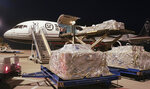 In this Jan. 30, 2020 photo released by China's Xinhua News Agency, workers unload a shipment of protective suits from a cargo plane at Wuhan Tianhe International Airport in Wuhan in central China's Hubei Province. Complicated logistics are part of a daily flow of food and other goods authorities say is sustaining Wuhan and surrounding cities with a total of 50 million people. Most are blocked from leaving in the most sweeping disease-control measures ever imposed. (Cheng Min/Xinhua via AP)