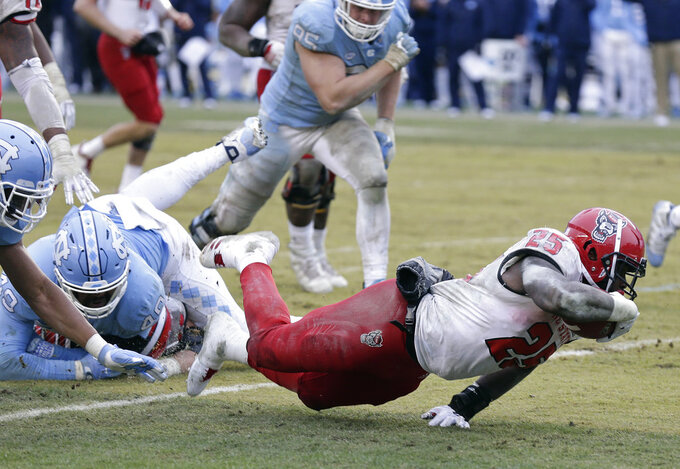 North Carolina State's Reggie Gallaspy II (25) struggles for extra yardage as North Carolina's Dominique Ross, left, and Jeremiah Clarke (49) attempt to tackle during overtime in an NCAA college football game in Chapel Hill, N.C., Saturday, Nov. 24, 2018. North Carolina State won 43-28. (AP Photo/Gerry Broome)
