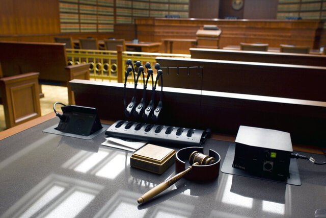 FILE - This Jan. 14, 2013, file photo shows a gavel sits on a desk inside the Court of Appeals at the Ralph L. Carr Colorado Judicial Center in Denver. The coronavirus pandemic has crippled the U.S. legal system, creating constitutional dilemmas as the accused miss their days in court. Judges from California to Maine have postponed trials and nearly all in-person hearings to keep crowds from packing courthouses. (AP Photo/Brennan Linsley, File)