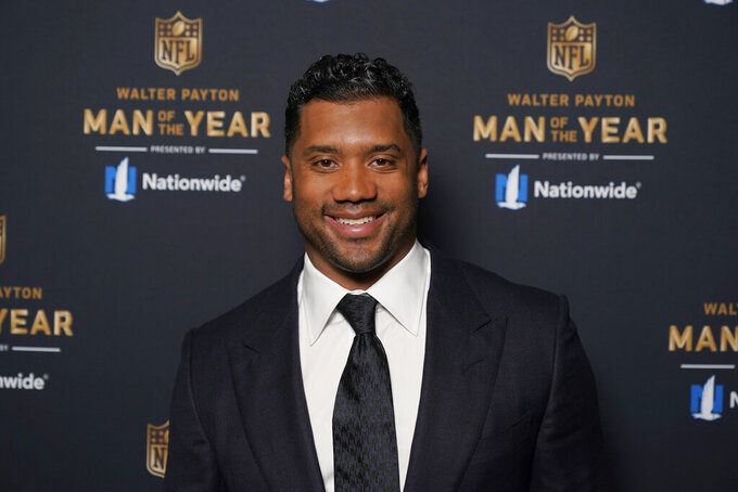 FILE - In this Friday, Feb. 5, 2021 file photo Seattle Seahawks quarterback Russell Wilson poses for a photo at the NFL Honors ceremony as part of Super Bowl 55  in Tampa, Fla. Wilson will return to N.C. State University, where he played football and baseball, this spring as a commencement speaker for the 2021 graduation ceremonies.  (AP Photo/Charlie Riedel, File)