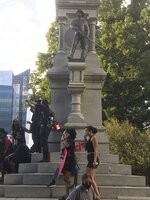 EDS NOTE: OBSCENITY - Protesters gather around the base of the Confederate monument on the grounds of the State Capitol, Saturday, May 30, 2020, in Raleigh, N.C., as people nationwide protested the Memorial Day death of George Floyd, who died in police custody in Minneapolis. (Lucille Sherman/The News & Observer via AP)