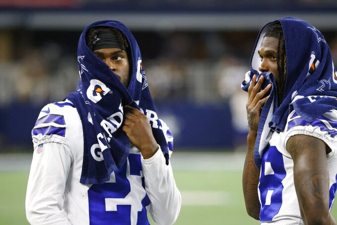 Dallas Cowboys cornerback Trevon Diggs, left, and wide receiver CeeDee Lamb, right, talk on the field after a preseason NFL football game against the Houston Texans in Arlington, Texas, Saturday, Aug. 21, 2021. (AP Photo/Ron Jenkins)