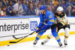St. Louis Blues' Tyler Bozak, left, fights off Boston Bruins' Brandon Carlo for control of the puck during the second period of an NHL hockey game Saturday, Feb. 23, 2019, in St. Louis. (AP Photo/Dilip Vishwanat)