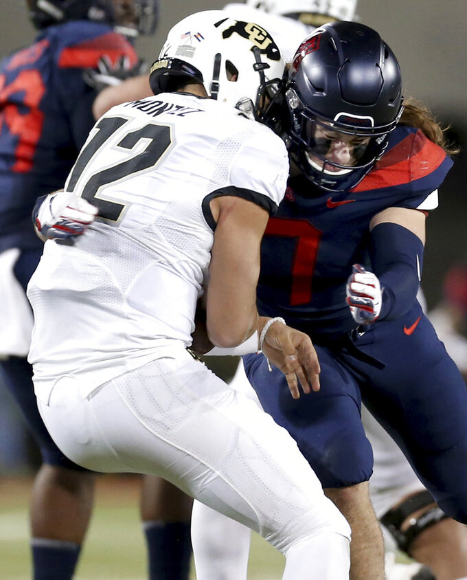 Arizona linebacker Colin Schooler (7) slams into Colorado quarterback Steven Montez (12) for a sack during the second quarter of an NCAA college football game Friday, Nov. 2, 2018, in Tucson, Ariz. (Kelly Presnell/Arizona Daily Star via AP)