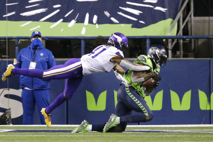 Seattle Seahawks' DK Metcalf, right, catches the ball in the end zone for a touchdown as Minnesota Vikings' Anthony Harris defends near the end of the second half of an NFL football game, Sunday, Oct. 11, 2020, in Seattle. (AP Photo/John Froschauer)