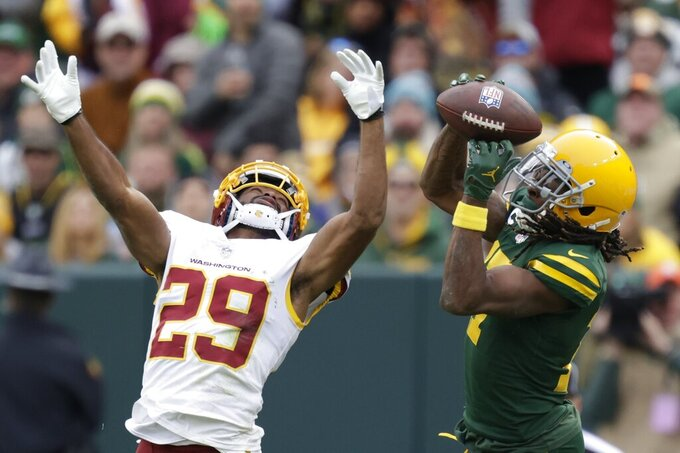 Green Bay Packers' Davante Adams catches a pass in front of Washington Football Team's Kendall Fuller during the second half of an NFL football game Sunday, Oct. 24, 2021, in Green Bay, Wis. (AP Photo/Matt Ludtke)