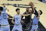 San Antonio Spurs forward LaMarcus Aldridge, second from right, is blocked from scoring by Memphis Grizzlies forward Brandon Clarke (15) and guard Dillon Brooks (24) during the second half of an NBA basketball game, in San Antonio, Monday, Nov. 11, 2019. (AP Photo/Eric Gay)