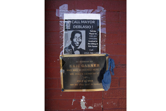 A sign and plaque are displayed on a wall, Tuesday, July 16, 2019, in the Staten Island borough of New York, at the sidewalk area where Eric Garner was apprehended by police in 2014. Federal prosecutors announced Tuesday, they will not bring charges against New York City police officer Daniel Pantaleo in the 2014 chokehold death of Garner. (AP Photo/Mark Lennihan)