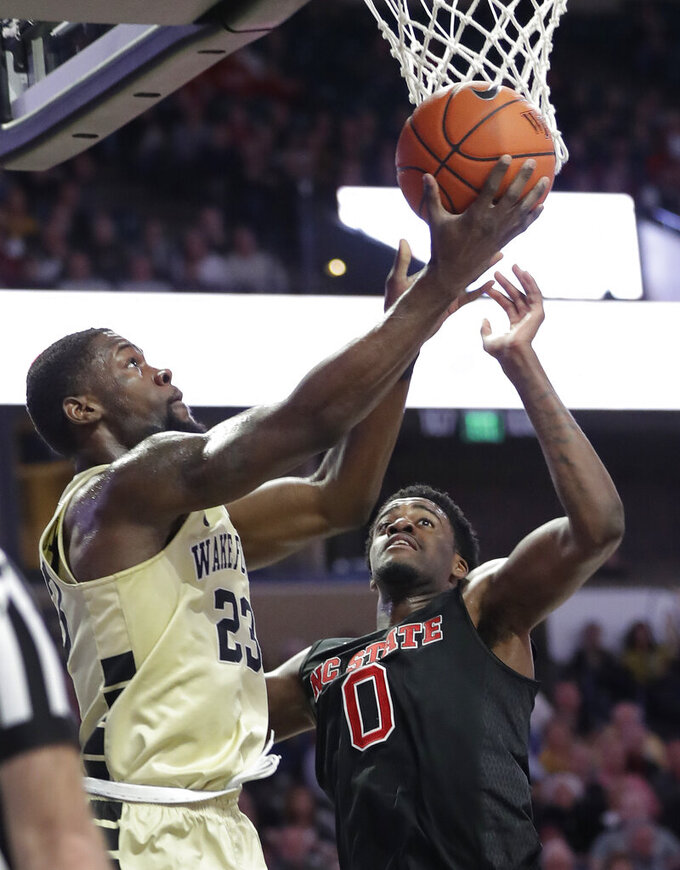 Wake Forest's Chaundee Brown (23) shoots in front of North Carolina State's DJ Funderburk (0) during the first half of an NCAA college basketball game in Winston-Salem, N.C., Tuesday, Jan. 15, 2019. (AP Photo/Chuck Burton)