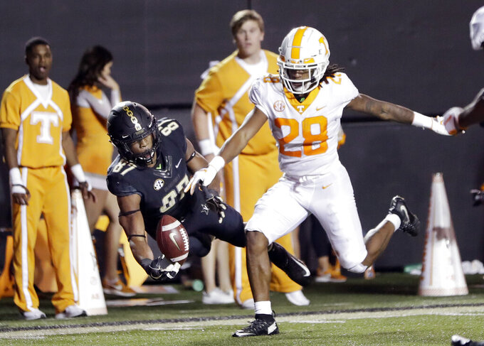 """FILE - In this Saturday, Nov. 24, 2018 file photo, Vanderbilt wide receiver Amir Abdur-Rahman (87) catches a 26-yard touchdown pass as he is defended by Tennessee defensive back Baylen Buchanan (28) in the second half of an NCAA college football game in Nashville, Tenn. Tennessee defensive back Baylen Buchanan has a spinal condition that leaves his status for this season uncertain. Buchanan started all 12 games for Tennessee last year but hasn't been participating in preseason practice. Tennessee coach Jeremy Pruitt says that Buchanan is being held out because """"basically we've discovered that he has kind of a narrowing of the spine."""" (AP Photo/Mark Humphrey, File)"""