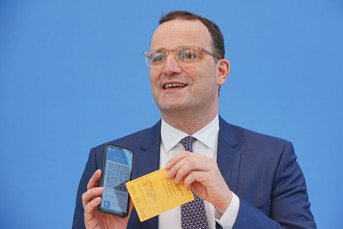 Jens Spahn (CDU), Federal Minister of Health, shows the Corona Warn app with a sample digital vaccination certificate as well as his own old vaccination certificate at the regular press conference on the Corona situation in Berlin, Germany, Thursday, June 10, 2021. One of the topics is the digital vaccination certificate. (Michael Kappeler/dpa via AP)