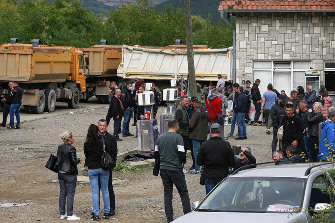 Local Serbs stand beside a road blocking the road leading to the northern Kosovo border crossing of Jarinje, Tuesday, Sept. 21, 2021. Tensions soared Monday when Kosovo special police with armored vehicles were sent to the border to impose a rule on temporarily replacing Serb license plates from cars while they drive in Kosovo. (AP Photo/Visar Kryeziu)