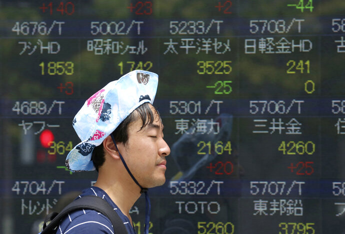 A man walks by an electronic stock board of a securities firm in Tokyo, Tuesday, July 17, 2018. Asian markets fell on Tuesday as mounting tensions over U.S. tariffs overshadowed data suggesting global growth was still on track. (AP Photo/Koji Sasahara)