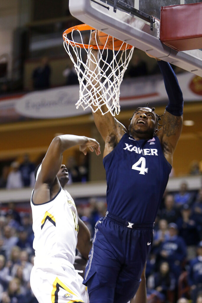 Xavier's Tyrique Jones goes up for a dunk next to Towson's Dennis Tunstall during the first half of an NCAA college basketball game during the Charleston Classic on Thursday, Nov. 21, 2019, in Charleston, S.C. (AP Photo/Mic Smith)