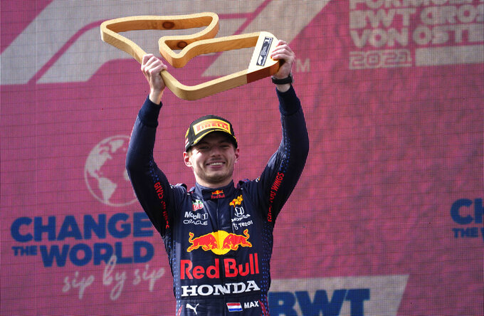Red Bull driver Max Verstappen of the Netherlands holds up his award on the podium after winning the Austrian Formula One Grand Prix at the Red Bull Ring racetrack in Spielberg, Austria, Sunday, July 4, 2021. (AP Photo/Darko Bandic)