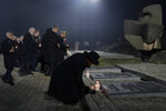 Britain's Duchess of Cornwall Camilla Parker-Bowles places a candle by the International Monument at the Auschwitz-Birkenau Nazi death camp in Oswiecim, Poland, Monday, Jan. 27, 2020. Heads of State and survivors of the Auschwitz-Birkenau death camp gathered Monday for commemorations marking the 75th anniversary of the Soviet army's liberation of the camp, using the testimony of survivors to warn about the signs of rising anti-Semitism and hatred in the world today. (AP Photo/Markus Schreiber)