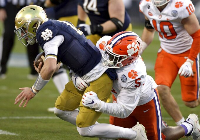 Clemson defensive end K.J. Henry, right, sacks Notre Dame quarterback Ian Book, left, during the Atlantic Coast Conference championship NCAA college football game, Saturday, Dec. 19, 2020, in Charlotte, N.C. (Jeff Siner/The News & Observer via AP)