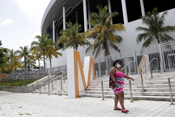 A woman wearing a protective face covering walks past Marlins Park, Monday, July 27, 2020, in Miami. The Marlins home opener against the Baltimore Orioles on Monday night has been postponed as the Marlins deal with a coronavirus outbreak that stranded them in Philadelphia. (AP Photo/Lynne Sladky)