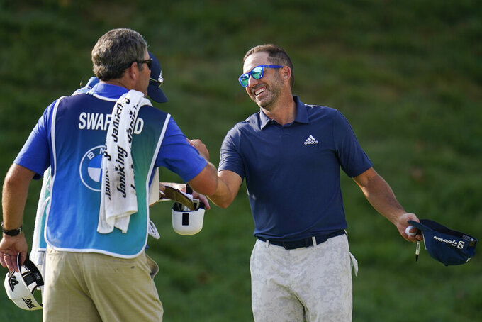 Sergio Garcia, right, of Spain, shakes hands with Hudson Swafford's caddie after completing his round during the third round of the BMW Championship golf tournament, Saturday, Aug. 28, 2021, at Caves Valley Golf Club in Owings Mills, Md. (AP Photo/Julio Cortez)