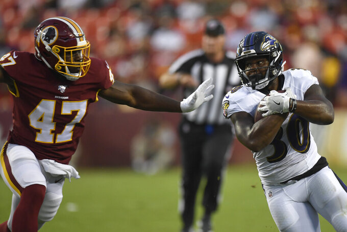 Baltimore Ravens running back Kenneth Dixon (30) holds the ball tight as he tries to run around Washington Redskins linebacker Andrew Ankrah (47) during the first half of an NFL preseason football game at FedEx Field in Landover, Md., Thursday, Aug. 29, 2019. (AP Photo/Susan Walsh)