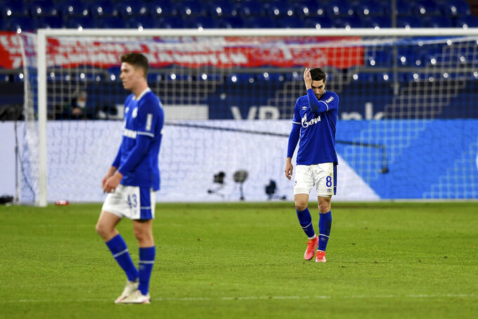 Schalke's Matthew Hoppe, left, and Suat Serdar react on the pitch during the German Bundesliga soccer match between FC Schalke 04 and Borussia Moenchengladbach at Veltins Arena, Gelsenkirchen, Germany, Saturday March 20, 2021. After loosing the match 0-3 Schalke is last in the Bundesliga with little to no hope of survival. (Guido Kirchner/dpa via AP)