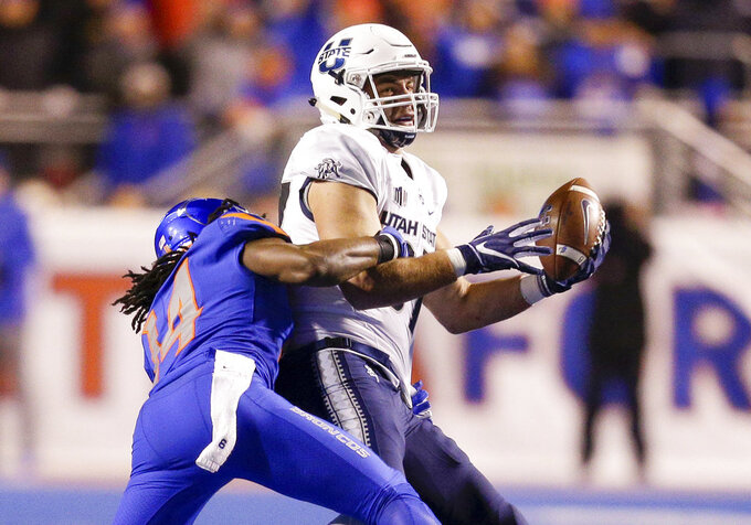 Utah State tight end Dax Raymond (87) reaches up to catch the ball as Boise State cornerback Tyler Horton (14) makes a tackle attempt in the second half of an NCAA college football game, Saturday, Nov. 24, 2018, in Boise, Idaho. Boise State won 33-24. (AP Photo/Steve Conner)