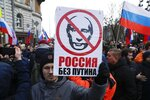 FILE - In this Feb. 29, 2020, file photo, a man holds a banner with a portrait of Russian President Vladimir Putin, reads