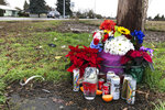 Flowers, candles, and other objects are shown at a memorial, Thursday, Dec. 12, 2019, at the scene where three Christmas tree farm workers from Guatemala were killed and others were injured in a van crash on Nov. 29, 2019 in Salem, Ore. Immigrant and worker advocates say the crash shed light on