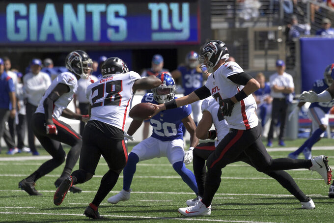 Atlanta Falcons quarterback Matt Ryan (2) hands off the ball to running back Mike Davis (28) during the first half of an NFL football game against the New York Giants, Sunday, Sept. 26, 2021, in East Rutherford, N.J. (AP Photo/Bill Kostroun)