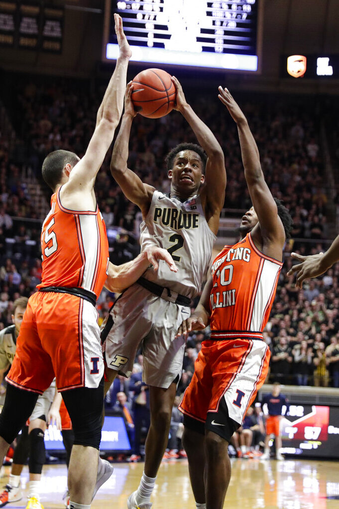 Purdue guard Eric Hunter Jr. (2) shoots between Illinois forward Giorgi Bezhanishvili (15) and guard Andres Feliz (10) during the second half of an NCAA college basketball game in West Lafayette, Ind., Tuesday, Jan. 21, 2020. Illinois defeated Purdue 79-62. (AP Photo/Michael Conroy)
