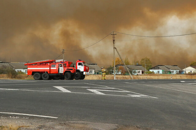 In this photo provided by the Russian Emergency Situations Ministry of Ryazan region press service, fire trucks are parked next to the village as smoke rises after explosions fire at the arsenal in the Ryazan region, about 250 kilometers (about 155 miles) southeast of Moscow, Wednesday, Oct. 7, 2020. A fire has engulfed a military arsenal in western Russia, triggering powerful explosions that have injured at least six and prompted the evacuation of thousands of residents from nearby villages. Authorities said that the fire that erupted Wednesday at the arsenal in the Ryazan region that holds munitions had been sparked by burning grass. (Russian Ministry of Emergency Situations of Ryazan region press service via AP)